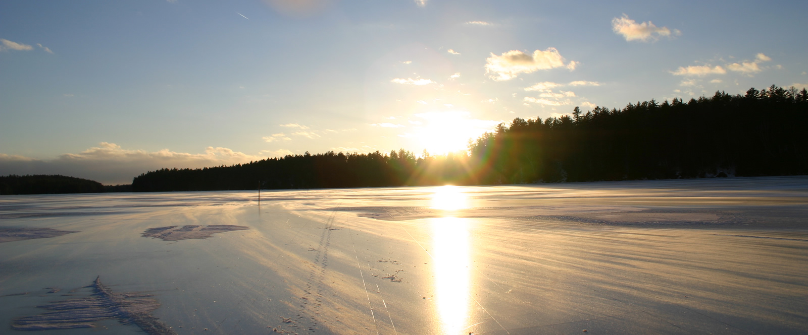 Late afternoon sun poking over trees on an icy lake