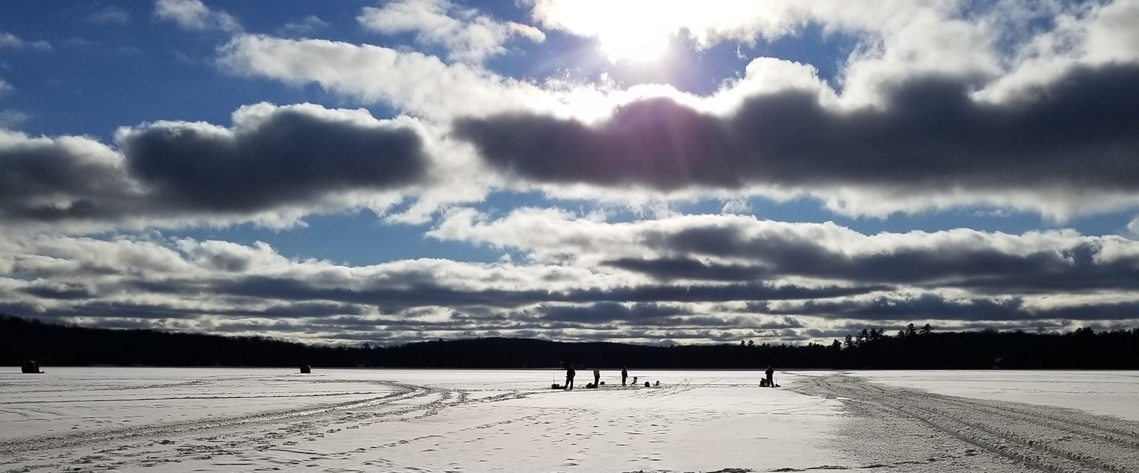 people ice fishing in the distance and clouds with the sun shining behind them
